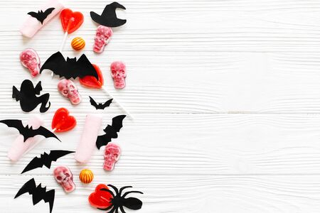 Halloween sweets flat lay. Halloween candy border with skulls, black bats, ghost, spider paper decorations on white wooden Banque d'images - 129713387