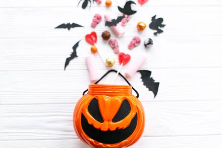 Halloween candy spilled from jack o lantern bucket with skulls, black bats, ghost, spider decorations on white wooden Banque d'images - 129713161