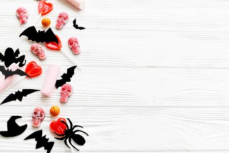 Halloween sweets flat lay. Halloween candy border with skulls, black bats, ghost, spider paper decorations on white wooden Banque d'images - 129713162