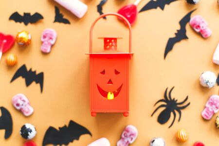 Halloween flat lay, jack o lantern and candy, skulls, black bats and ghost paper decorations on yellow Banque d'images - 129713157