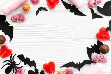 Halloween sweets flat lay. Halloween candy frame with skulls, black bats, ghost, spider paper decorations on white wooden Banque d'images - 129713167