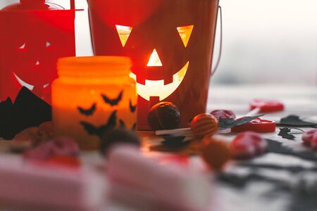Halloween jack o lantern bucket, glowing candle, festive candy, skulls, black bats, ghost, spider decorations on white wooden Banque d'images - 129713166