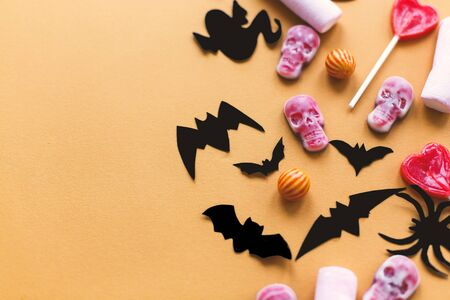Halloween candy, skulls, black bats, ghost, spider paper decorations on yellow Banque d'images - 129713169
