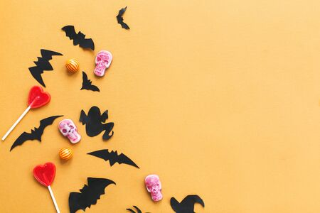 Halloween flat lay, copy space. Halloween candy, skulls, black bats, ghost, spider paper decorations on yellow Banque d'images - 129713176