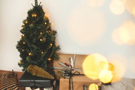 Christmas tree with festive stylish gifts in golden lights bokeh in white room. Happy Holidays. Merry Christmas.Winter holidays preparation. Copy space. Seasons Greeting Stock Photo