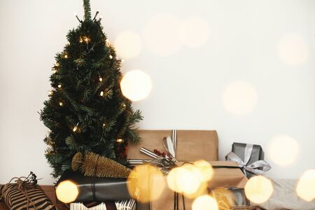 Christmas tree with festive stylish gifts in golden lights bokeh in white room. Happy Holidays. Merry Christmas.Winter holidays preparation. Copy space. Season's Greeting