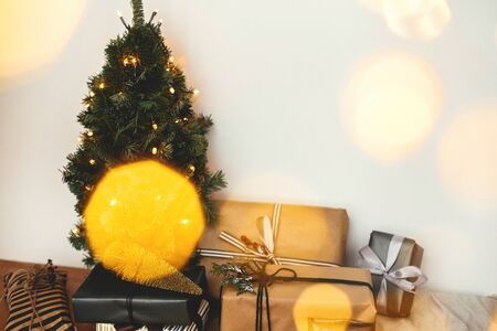 Christmas tree with festive stylish gifts in golden lights bokeh in white room. Merry Christmas.Winter holidays preparation. Copy space. Happy Holidays. Season's Greeting Stock Photo