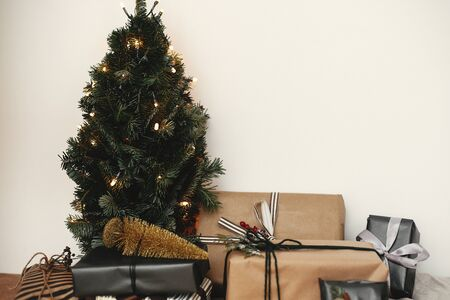 Stylish gift boxes under Christmas tree with festive golden lights in white room. Merry Christmas. Winter holidays preparation. Happy Holidays .Copy space. Seasons Greeting