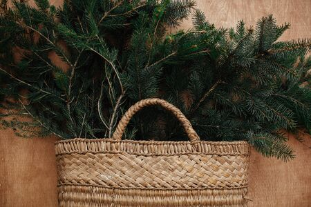 Rustic basket with fir branches on rustic wooden background. Flat lay. Winter holiday preparations. Slow living. Seasons greeting. Stock Photo