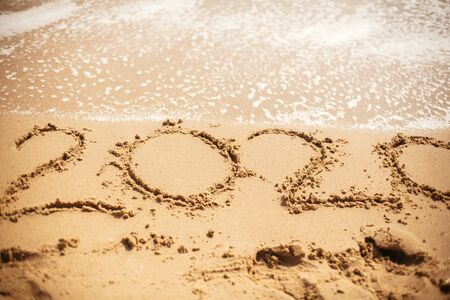 2020 New Year. 2020 written on sandy beach with wave foam at sea beach. Happy New Year. Tropical celebration. Inscription on golden sand.