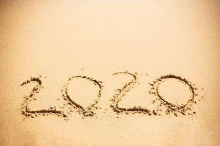 Happy New Year 2020, handwritten on sandy beach. 2020 numbers inscription on golden sand at sea beach. Tropical celebration.