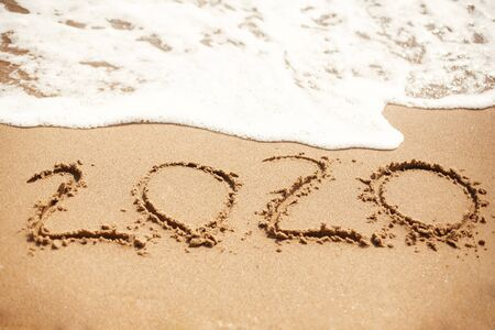 Happy New Year 2020, handwritten on sandy beach. 2020 numbers inscription on golden sand and waves foam at sea beach. Tropical celebration