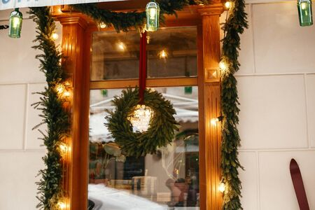 Stylish christmas wreath with fir branches and lights at front window of store at holiday market in city street. Space for text. Rustic decoration. Christmas street decor.