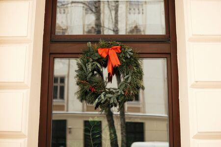 Christmas street decor. Stylish christmas wreath with red bow and berries at front of store at holiday market in city street. Space for text. Rustic decoration Stock Photo