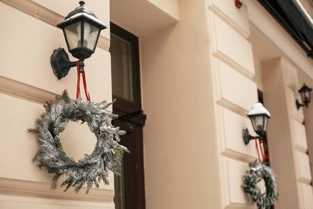 Christmas street decor. Stylish christmas rustic wreaths on lantern at front store at holiday market in city street. Space for text. Rustic decoration