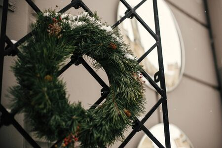 Christmas street decor. Stylish christmas rustic wreath with pine cones and berries at front doors of store at holiday market in city street. Space for text. Rustic decoration Stock Photo