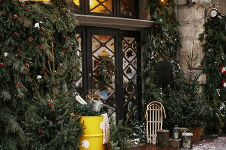 Stylish christmas tree with red berries, wreath on doors and wooden sleigh at front of store at holiday market in city street. Christmas street decor. Space for text. Rustic decoration Stock Photo