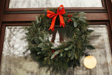 Stylish christmas wreath with red bow and berries at front of store at holiday market in city street. Space for text. Rustic decoration. Christmas street decor. Archivio Fotografico