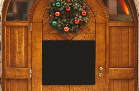 Stylish christmas wreath with red and green baubles and empty board with copy space on rustic wooden doors at holiday market in city street. Christmas template. Space for text Stock Photo