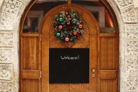 Christmas street decor. Stylish christmas wreath with red and green baubles and empty board with copy space on rustic wooden doors at holiday market in city street. Space for text.  template