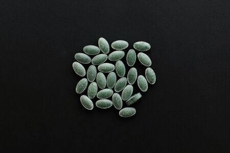 Chlorophyll tablets on black dark background. Flat lay. Dietary supplements. Health support and treatment. Biologically active additives. Detox pills Reklamní fotografie