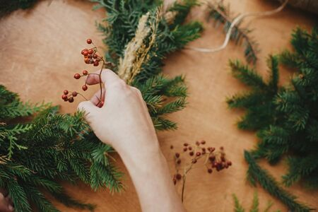 Hands holding berries and  fir branches, pine cones, thread on wooden table. Christmas wreath workshop. Authentic stylish still life. Making rustic Christmas wreath.