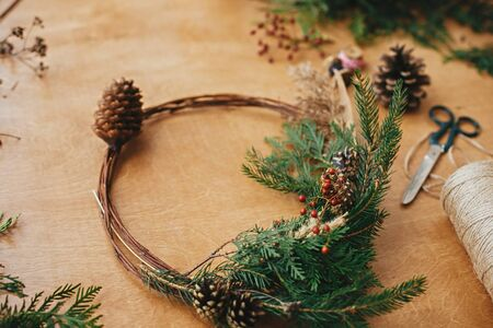 Rustic Christmas wreath. Creative christmas wreath with fir branches, berries, pine cones and herbs with scissors and thread on rural wooden table. Happy holidays. Workshop