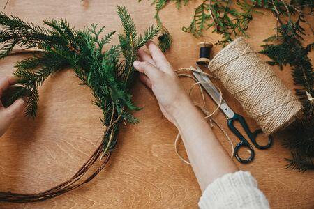 Hände, die Tannenzweige und Tannenzapfen, Faden, Schere auf Holztisch halten. Rustikalen Weihnachtskranz flach machen. Details zum Workshop zum Basteln von Weihnachtskränzen
