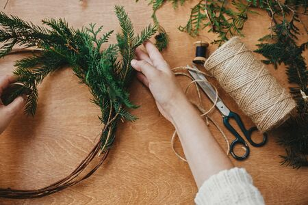 Hands holding fir branches and pine cones, thread, scissors on wooden table. Making rustic christmas wreath flat lay. Details for workshop of making christmas wreath