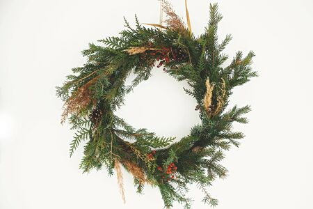 Christmas rustic wreath. Creative rural christmas wreath with fir branches, berries, pine cones and herbs hanging on white wall in room. Copy space. Season's greetings.