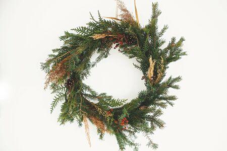 Rustikaler Weihnachtskranz. Kreativer ländlicher Weihnachtskranz mit Tannenzweigen, Beeren, Tannenzapfen und Kräutern, die an der weißen Wand im Zimmer hängen. Platz kopieren. Die Grüße der Jahreszeit. Standard-Bild