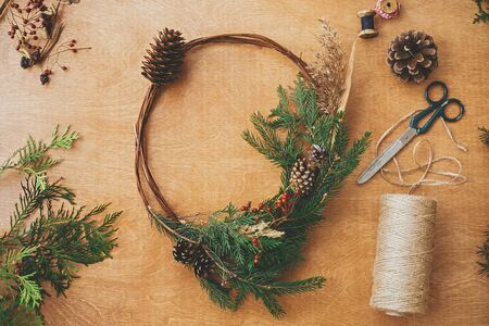 Rustic Christmas wreath, flat lay. Creative christmas wreath with fir branches, berries, pine cones and herbs with scissors and thread on rural wooden table. Happy holidays. Workshop Stock Photo