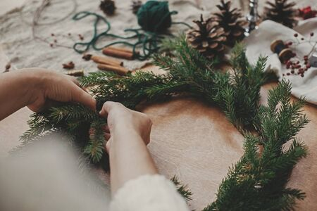 Making rustic Christmas wreath. Hands holding fir branches, and pine cones, thread, berries, scissors on wooden table. Christmas wreath workshop. Authentic stylish still life
