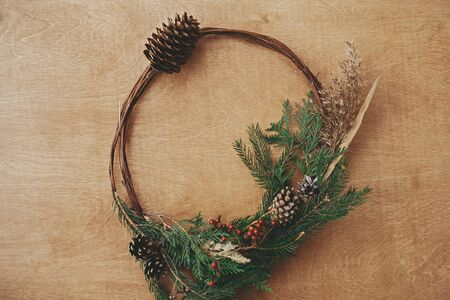 Christmas rustic wreath flat lay. Creative rural christmas wreath with fir branches, berries, pine cones and herbs on wooden table. Copy space. Seasons greetings