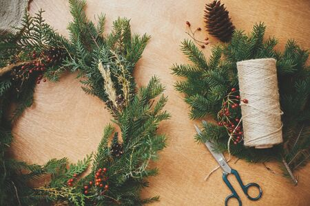 Rustic Christmas wreath flat lay. Fir branches, pine cones, thread, berries, scissors on wooden table. Christmas wreath workshop. Authentic stylish still life. Merry Christmas Stock Photo