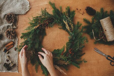 Hands holding christmas wreath with fir branches, berries, pine cones, and thread, scissors on rural wooden table. Rustic Christmas wreath, flat lay. Christmas wreath workshop Stock Photo