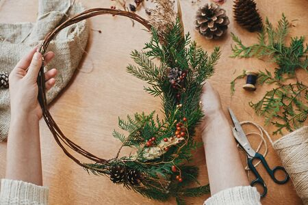 Hands holding rustic christmas wreath with pine cones, berries, fir branches, thread, scissors on wooden table.  Authentic rural wreath. Christmas wreath workshop. Stock Photo