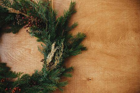 Rustikaler Weihnachtskranz flach. Kreativer ländlicher Weihnachtskranz mit Tannenzweigen, Beeren, Tannenzapfen und Kräutern auf Holztisch. Platz kopieren. Die Grüße der Jahreszeit