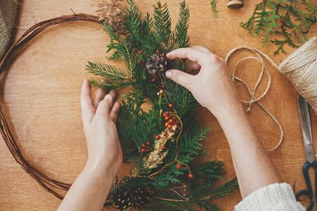 Making rustic christmas wreath flat lay. Hands holding fir branches and pine cones, berries, thread, scissors on wooden table. Details for workshop of making christmas wreath 免版税图像
