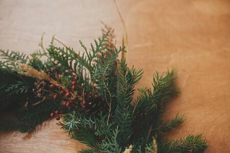 Christmas rustic wreath closeup. Creative rural christmas wreath details with fir branches, berries, pine cones and herbs on wooden table. Copy space. Seasons greetings. 免版税图像