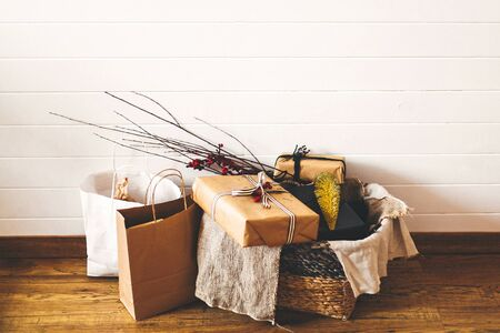 Stylish christmas gift boxes on wooden floor under christmas tree. Presents and ornaments in rustic basket and paper bags. Holiday shopping. Wrapped gifts