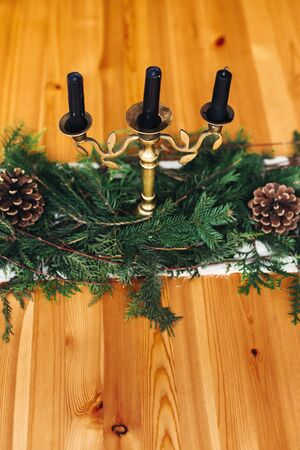 Stylish rustic christmas arrangement for festive dinner. Fir branches with pine cones and vintage candlestick with black candles on wooden table. Copy space. Christmas rural table decor