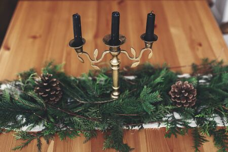 Stylish rustic christmas arrangement for festive dinner. Fir green branches with pine cones and vintage candlestick with black candles on wooden table. Christmas rural decor, table setting