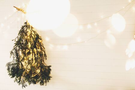Modern christmas tree made of pine branches with golden festive lights hanging on white wooden wall. Alternative eco christmas tree concept. Scandinavian minimal decor. Space 免版税图像