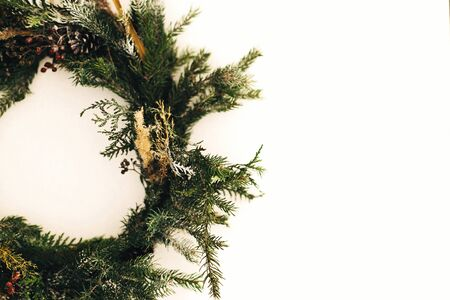 Rustic christmas wreath made of pine branches, cones and berries closeup  on white wall. Stylish christmas wreath. Scandinavian minimal decor. Seasons greetings