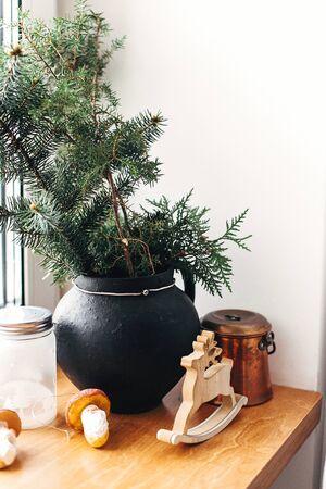 Stylish christmas decor on wooden windowsill. Pine branches with vintage bauble, wooden deer, lantern, mushroom toys on rustic windowsill. Cozy winter decoration