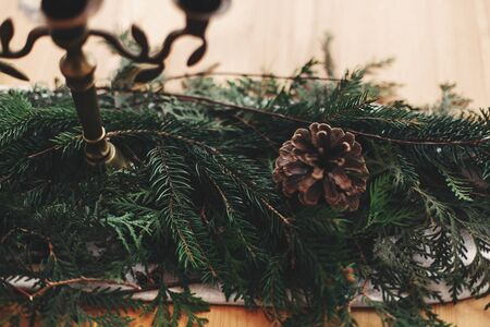 Stylish rustic christmas arrangement for festive dinner closeup. Fir branches with pine cones and vintage candlestick with candles on linen cloth on wooden table. Christmas rural decor
