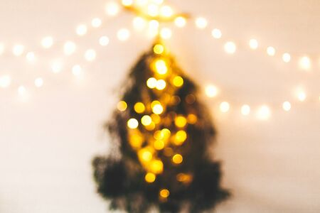 Abstract christmas tree. Blurred image of christmas tree made of pine branches with golden festive lights hanging on white wall. Alternative christmas tree. Scandinavian minimal decor