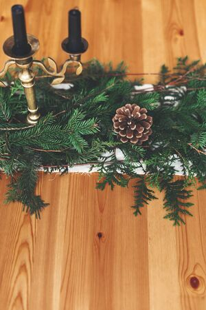 Stylish rustic christmas arrangement for festive dinner. Fir branches with pine cones and vintage candlestick with  black candles on wooden table. Christmas rural table decor for feast 免版税图像