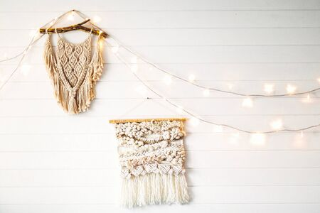 Macrame hanging on white wooden wall with lights. Stylish boho decor, modern wall hanging. Modern interior decor in scandinavian or rustic room. 免版税图像